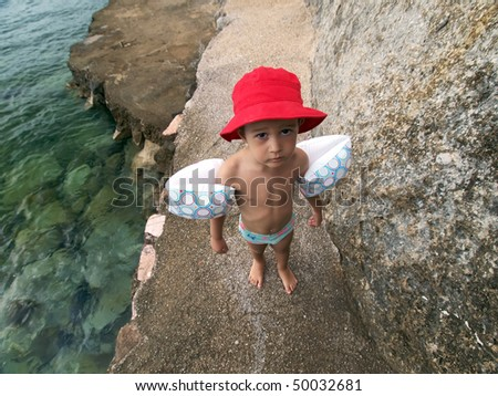 Little boy with red hat on a rocky beach - stock photo