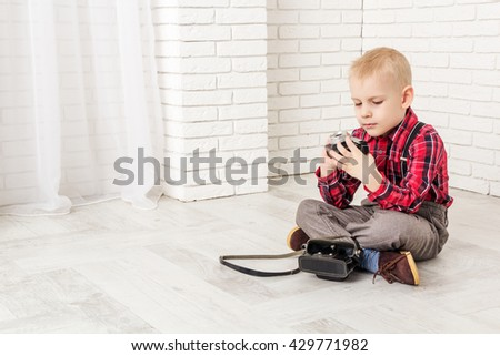 little boy with retro camera he sits on the floor