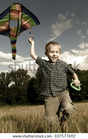 Little boy with rite flying over his head running across the field - stock photo