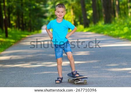 little boy with skateboard. little boy having fun with skateboard outdoors. little boy riding on his stomach on skateboard - stock photo