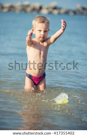 Little boy with snorkel by the sea. Cute little kid wearing mask and flippers for diving at sand tropical beach. Ocean coast. - stock photo