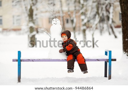 little boy with snowman - stock photo
