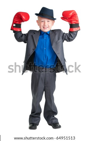 Little boy with suit and hat raising his hands in boxer gloves as winner