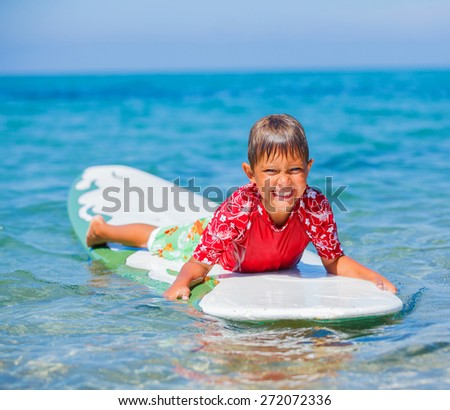 Little boy with surf board learning surfing - stock photo