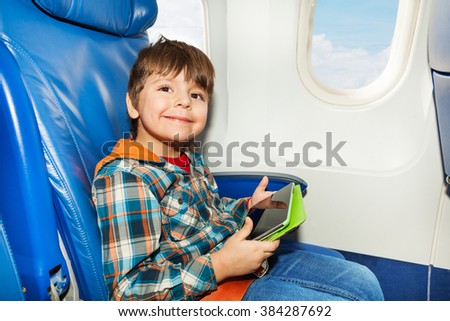 Little boy with tablet pc in airplane chair - stock photo