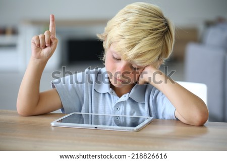 Little boy with tablet raising hand - stock photo