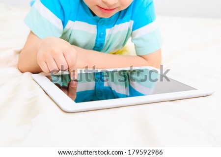 Little boy with tablet. Selective focus on child finger - stock photo
