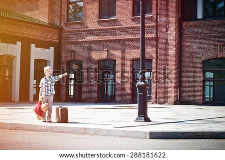 little boy with teddy bear toy and suitcase  shows forward, stands on the sunny deserted street
