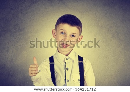 Little boy with thumb up gesture and tongue isolated over white background.Portrait of confident happy little boy showing thumbs up gesture wearing costume  isolated over white - stock photo
