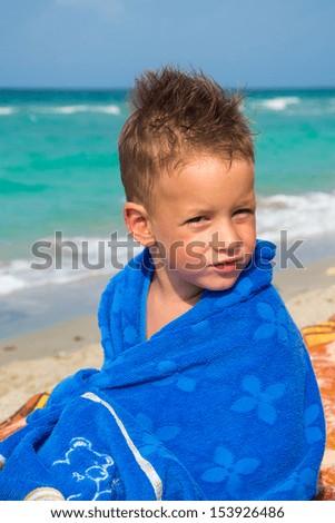 Little boy with towel on beach - stock photo