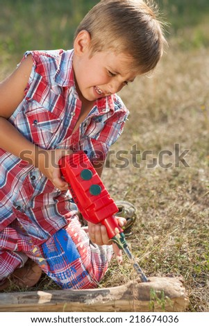 Little boy with toy hand tools drill. Emotional, hard at work outside.