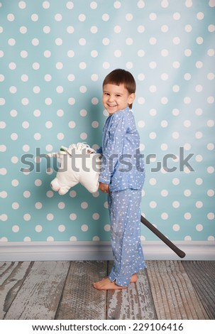 Little boy  with toy horse. - stock photo