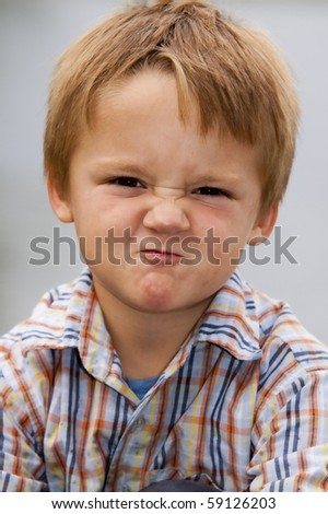 Little boy with very grumpy face expression - stock photo