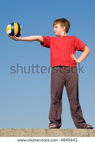 little boy with volleyball ball on a blue sky