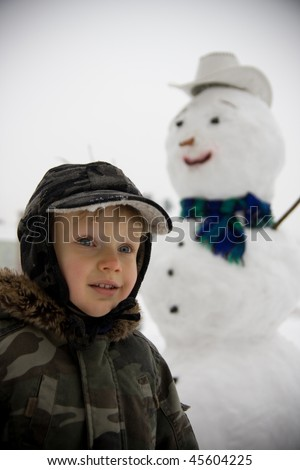 Little Boy with white snowman in background.