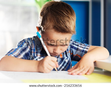 little boy working very hard on homework - stock photo