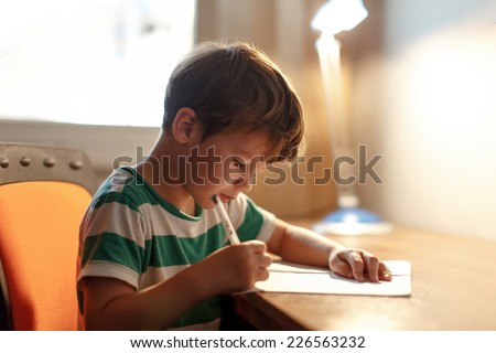 Little boy write to blank paper on desk - stock photo