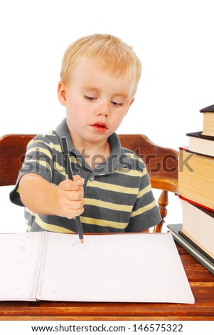 Little boy writes in his notebook, pretending to be a school student - stock photo