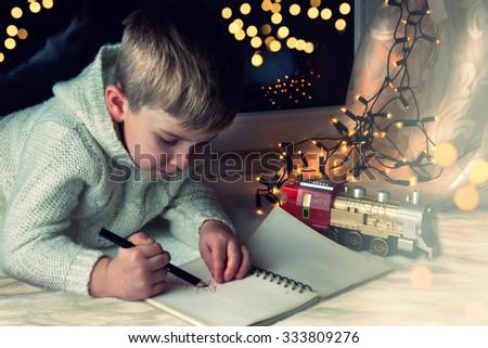 Little boy writes letter to Santa. - stock photo