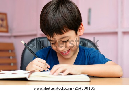 Little boy writing homework in the room with smiling - stock photo
