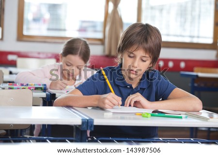 Little boy writing notes while classmate studying in background at classroom - stock photo