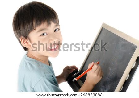 Little boy writing on blackboard - stock photo