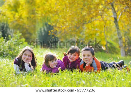Little boys and girls laying down on grass - stock photo