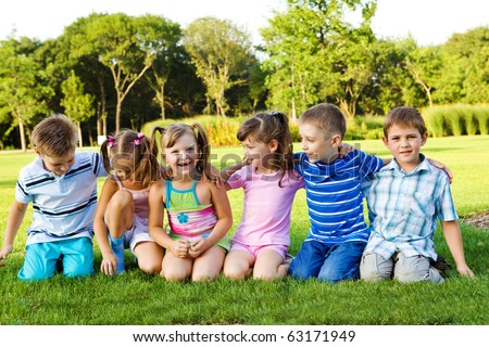 Little boys and girls sitting on grass and embracing - stock photo