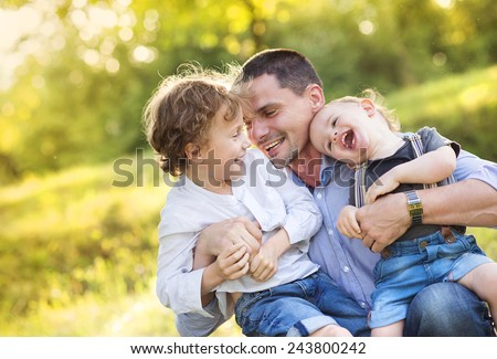 Little boys and their dad enjoying their time together outside in nature - stock photo