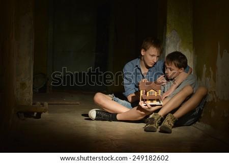 Little boys in a dark cellar - stock photo