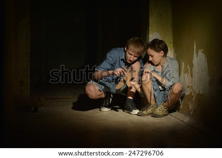 Little boys in a dark cellar with toy plane - stock photo