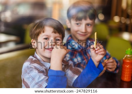 Little boys in fast food restaurant behind glass eating french fries and smile - stock photo