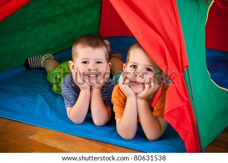 Little boys lying inside colorful tent and looking forward - stock photo