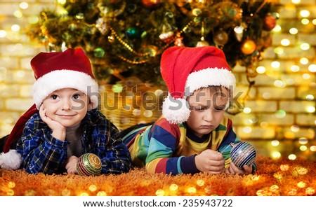 Little boys near a Christmas tree. Children in cap of Santa - stock photo