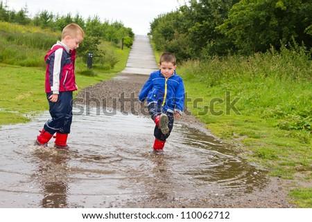 little boys splashing in  puddles on a rainy day - stock photo