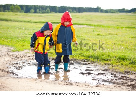 Little boys walking in a mud puddle - stock photo