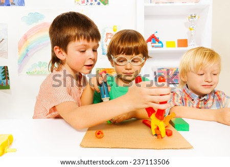 Little boys with toy pliers in classroom - stock photo