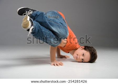 little break dancer showing his skills on grey background. Hip hop dancer boy performing isolated over dark background