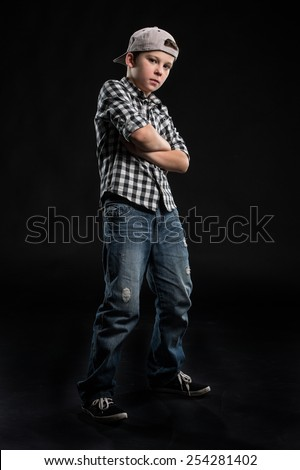 little break dancer standing arms crossed on black background. Hip hop dancer boy performing isolated over dark background  - stock photo