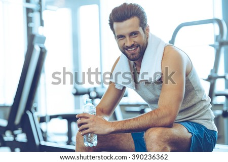 Little break. Handsome young men in sportswear holding water bottle and looking at camera with smile while sitting at gym - stock photo