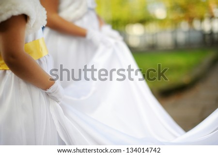 Little bridesmaids holding bride's wedding dress - stock photo