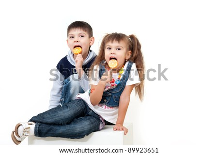 Little brother and sister eating tasty candies isolated on white