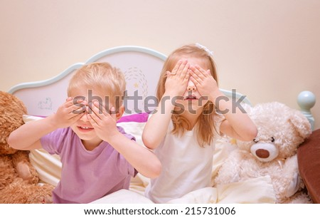 Little brother and sister play in hide and seek at home, covered eyes with hands, having fun together, family relationship, happy childhood concept - stock photo