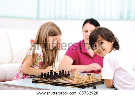 Little brother and sister playing chess at home with their mother - stock photo