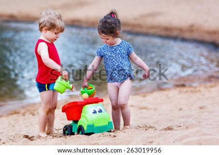 Little brother and sister playing together with sand toys near city lake on hot summer day. Active outdoors leisure with kids in summer, on sunny day. - stock photo