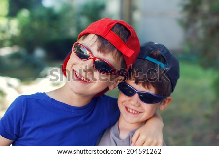Little brothers in sunglasses laughing, outdoor portrait