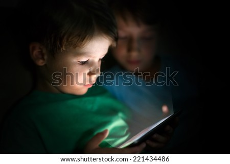 Little brothers playing on tablet at night - stock photo