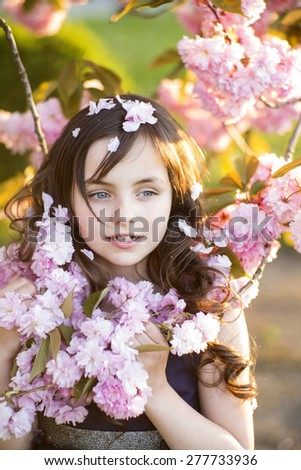 Little brunette girl looking away standing amid pink japanese cherry blossom in broad daylight in the park, vertical picture - stock photo