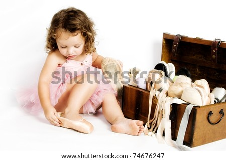 Little brunette girl trying on ballet shoes