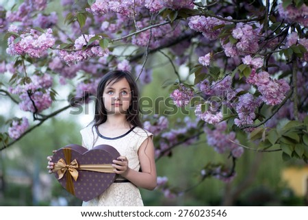 Little brunette smiling girl looking away holding big brown heart shaped present box standing among japanese cherry blossom in the park copyspase, horizontal picture  - stock photo